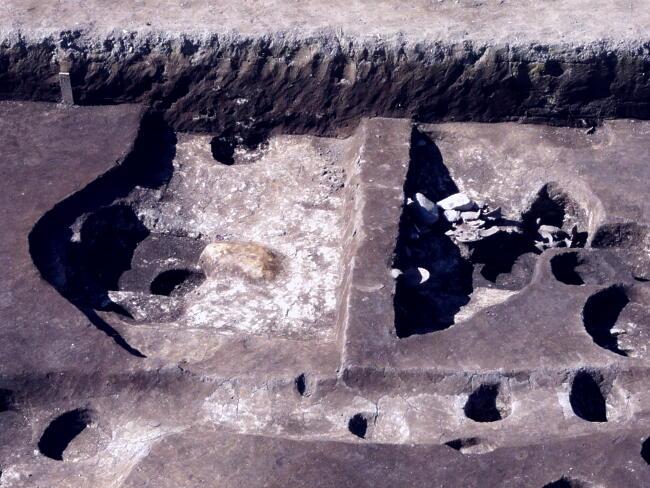 調査区北端の竪穴遺構。右半部で土器が多数出土しています。左半部の橙色部分は焼土です。