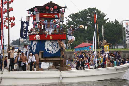 波おだやかな大淀の浦を山車が行く祇園祭